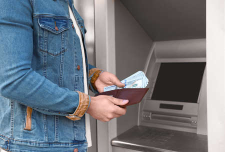 Young man with money near cash machine outdoors, closeup Stok Fotoğraf