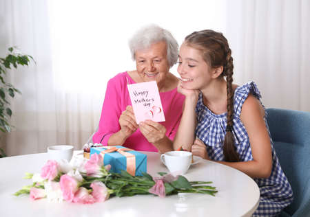 Preteen girl congratulating her granny at home. Happy Mother's Day 免版税图像