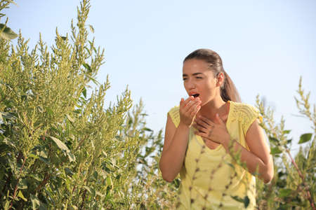 Young woman suffering from ragweed allergy outdoors Stock Photo
