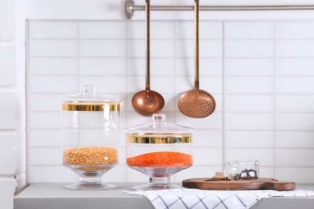 Jars with cereals on light grey table in modern kitchen Stok Fotoğraf