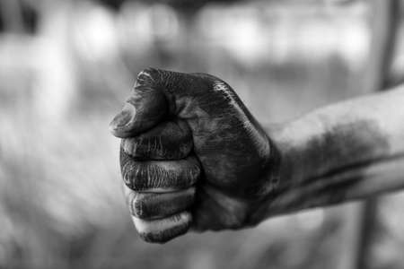 Dirty worker clenching fist on blurred background, closeup of hand. Black and white effect