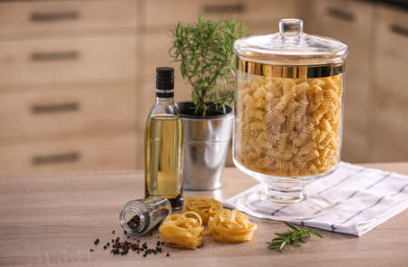 Raw pasta on wooden table in modern kitchen