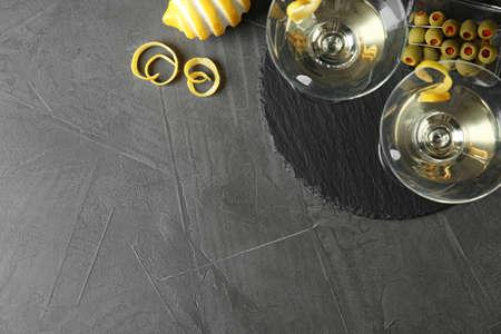Verres de cocktail Lemon Drop Martini avec zeste sur table grise, mise à plat. Espace pour le texte