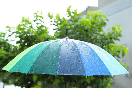 Open colorful umbrella outdoors on rainy day Stock Photo