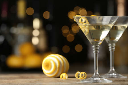 Verres de cocktail Lemon Drop Martini avec zeste sur table en bois sur fond flou. Espace pour le texte