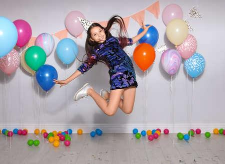 Happy girl having fun at birthday party indoors
