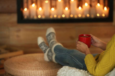 Woman with cup of hot drink near decorative fireplace indoors, closeup. Winter atmosphere