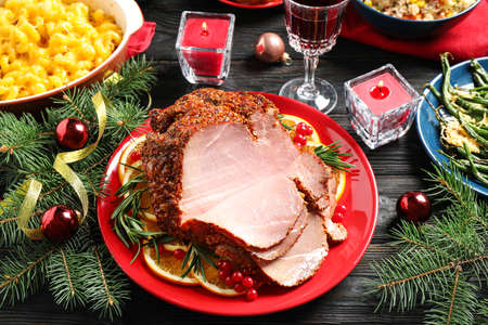 Plate with delicious ham served on dark wooden table. Christmas dinner Stock Photo