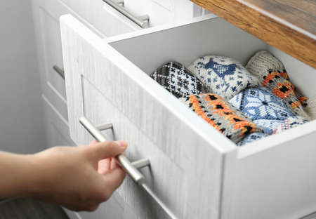 Woman opening drawer with warm socks indoors, closeup