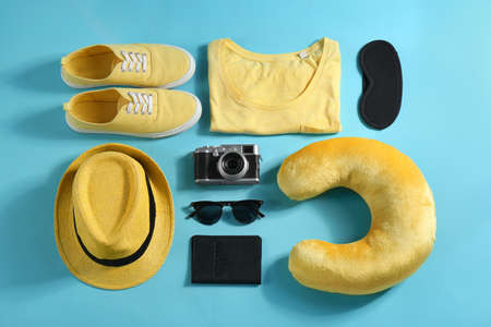 Flat lay composition with travel pillow and tourist stuff on light blue background 写真素材