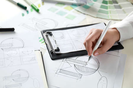 Female designer working at wooden table, closeup