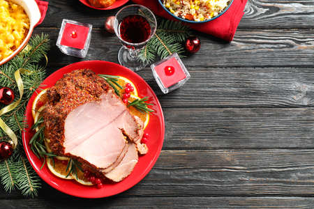 Flat lay composition with delicious ham served on dark wooden table, space for text. Christmas dinner