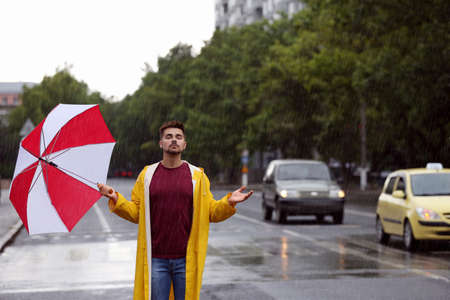 Handsome young man with bright umbrella outdoors on rainy day Stock Photo