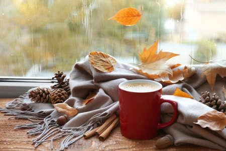 Tasse heißes Getränk, Schal und Herbstlaub auf der Fensterbank. Gemütliche Atmosphäre