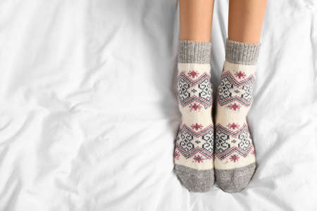 Woman wearing knitted socks on white fabric, top view with space for text. Warm clothes Stockfoto