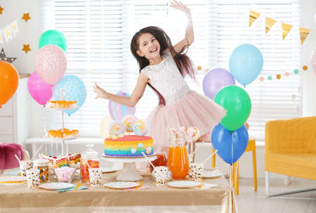 Happy girl at table with treats in room decorated for birthday party
