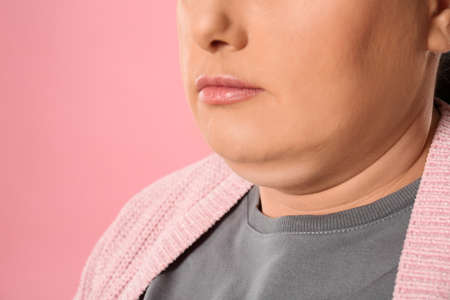 Woman with double chin on pink background, closeup