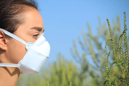 Young woman suffering from ragweed allergy outdoors, closeup Stock Photo