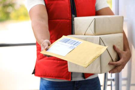 Jeune coursier tenant des colis sur le pas de la porte, gros plan. Service de livraison