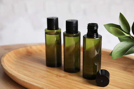 Mini bottles with cosmetic products on wooden tray against white background