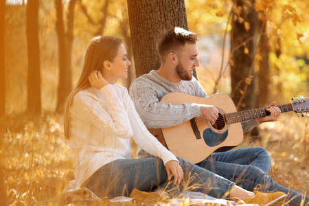Young couple with guitar in autumn park