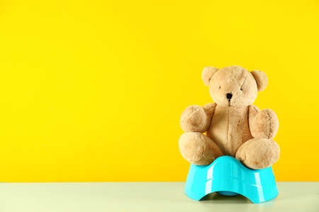 Teddy bear with blue potty on table against yellow background, space for text. Toilet training