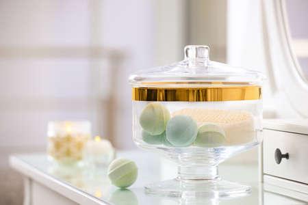 Jar with bath bombs and bath sponge on dressing table indoors