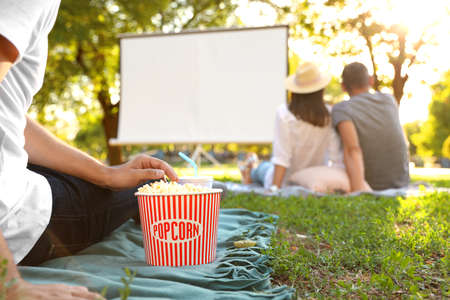 Young man with popcorn watching movie in open air cinema, closeup. Space for text