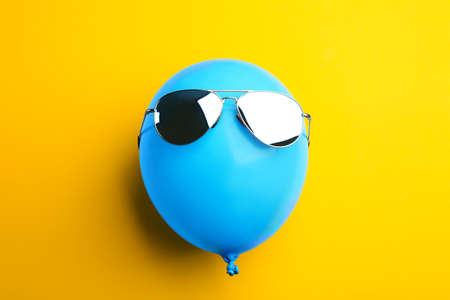 Balloon with stylish sunglasses on yellow background, top view Stock Photo