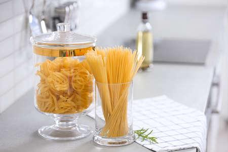 Raw pasta on light grey table in modern kitchen