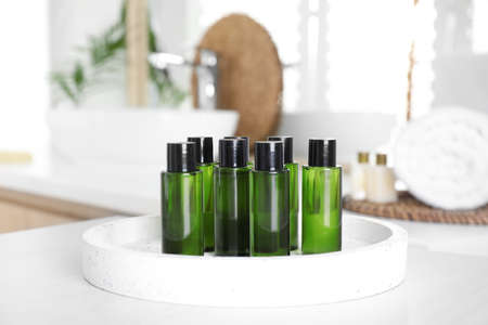 Mini bottles with cosmetic products on white table in bathroom