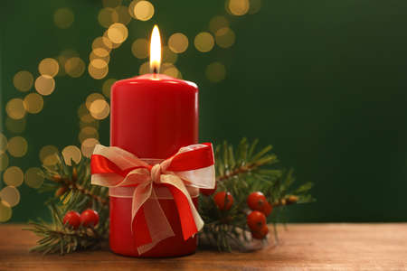 Beautiful Christmas composition with burning candle on table against blurred lights. Space for text Stock Photo