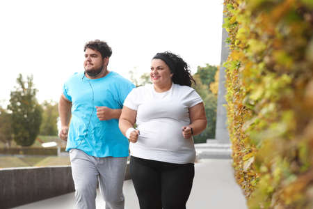 Overweight couple running together in park