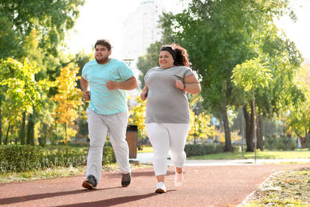 Overweight couple running together in park on sunny day