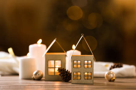 Composition with house shaped candle holder on wooden table against blurred background. Christmas decoration