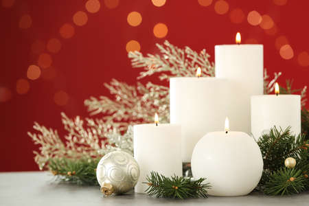 Burning white candles and Christmas decor on table against red background with bokeh effect Stock fotó