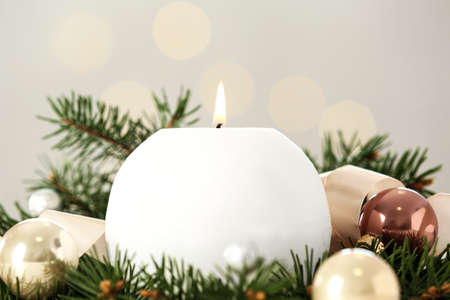 Burning white candle with Christmas decor on blurred background