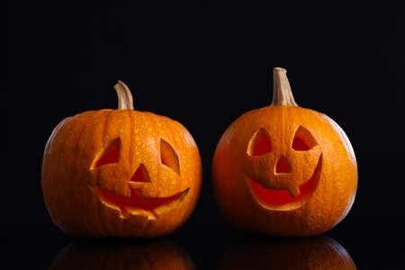 Pumpkin heads on black background. Jack lantern - traditional Halloween decor Stock fotó