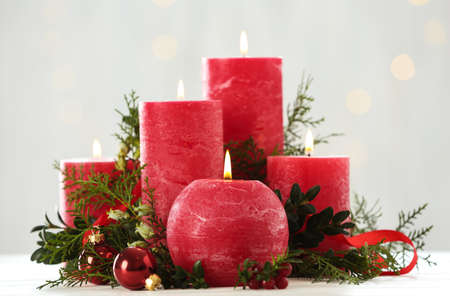 Burning red candles with Christmas decor on table against blurred lights