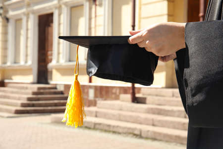 Student with graduation hat outdoors on sunny day, closeup