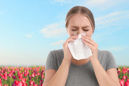 Young woman suffering from allergy and blooming field on background