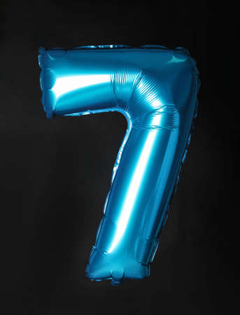 Blue number seven balloon on black background