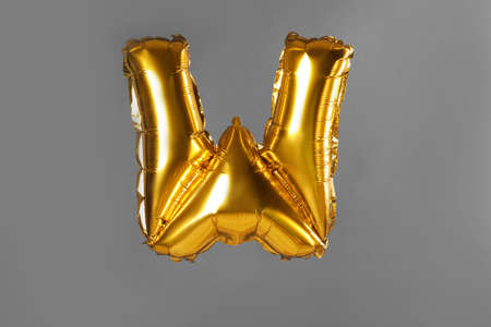 Golden letter W balloon on grey background Stock Photo