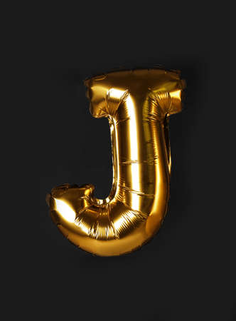 Golden letter J balloon on black background