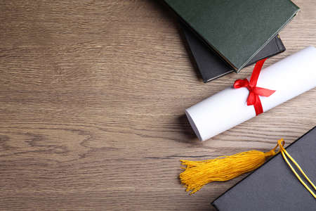Flat lay composition with graduation hat and student's diploma on wooden table, space for text