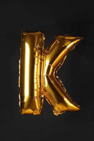 Golden letter K balloon on black background