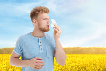 Young man suffering from allergy and blooming field on background