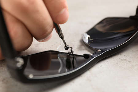 Handyman repairing sunglasses with screwdriver at grey table, closeup