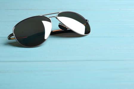 Stylish sunglasses on blue wooden background. Fashionable accessory Banco de Imagens