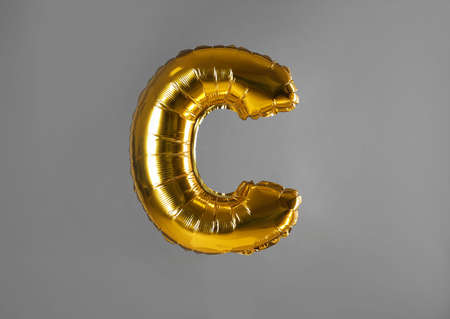 Golden letter C balloon on grey background